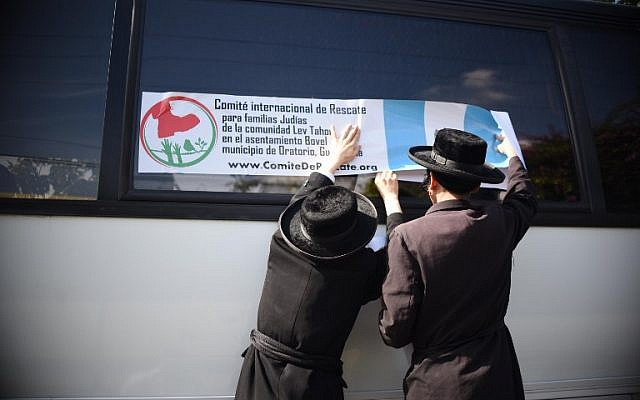 Members of an Orthodox Jewish community put a label from the 'International Rescue Committee for Jewish Families of the Lev Tahor Settlement' on the window of a bus in Guatemala city on September 25, 2016.  (AFP PHOTO / JOHAN ORDONEZ)