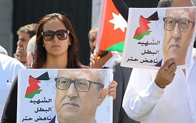 Protesters hold portraits of prominent Jordanian writer Nahed Hattar, who was shot dead the previous day outside an Amman court, during a demonstration in front of the prime minister's offices on September 26, 2016. (AFP PHOTO / Khalil MAZRAAWI)