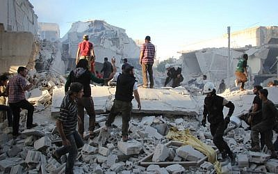 Syrian men search for people under the rubble of destroyed buildings following a reported air strike on the rebel-held northwestern city of Idlib on September 29, 2016. (AFP PHOTO / Omar haj kadour).