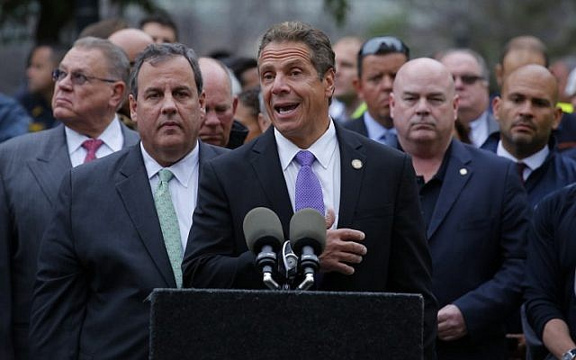 New York Governor Andrew Cuomo (C), flanked by New Jersey Governor Chris Christie (R), speaks during a press conference outside the New Jersey transit rail station in Hoboken, New Jersey September 29, 2016. (AFP PHOTO / KENA BETANCUR)
