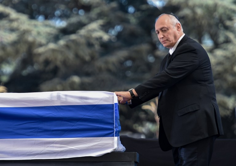 Chemi Peres, son of former Israeli president and prime minister Shimon Peres, pauses in front of his father's coffin after speaking during his funeral on September 30, 2016, at Jerusalem's Mount Herzl national cemetery.(AFP PHOTO / NICHOLAS KAMM)