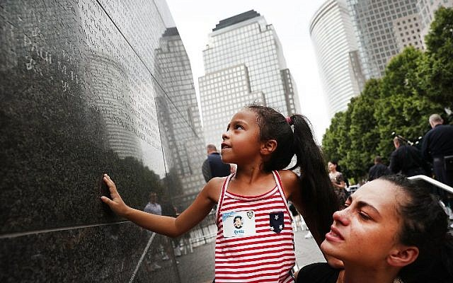 Bernadette Ortiz holds up her daughter Adriana as she looks for the name of her grandfather, fallen New York City police officer Edwin Ortiz, at a wall commemorating fallen officers on September 9, 2016 in New York City. (Spencer Platt/Getty Images/AFP)