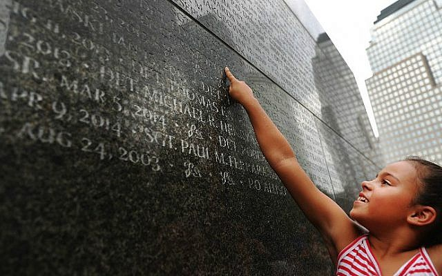 Gabriella Ortiz reaches up to point to the name of her grandfather, fallen New York City police officer Edwin Ortiz, at a wall commemorating officers who fell on or in the wake of the September 11, 2001 attacks, on September 9, 2016 in New York City. (Spencer Platt/Getty Images/AFP)