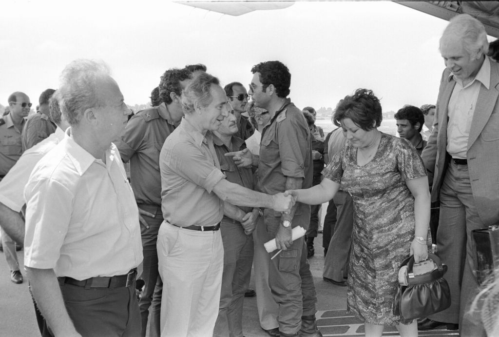 Then-defense minister Shimon Peres, along with former prime minister Yitzhak Rabin, meets the hostages released from Entebbe as they land in Israel on July 4, 1976.  (Uri Herzl Tzchik/IDF Spokesperson's Unit/Defense Ministry Archives)