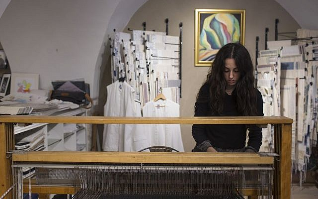 Adi Yair weaving on the loom of a prayer shawl shop in the Cardo of Jerusalem's Jewish Quarter in 2015 (Courtesy Adi Yair)