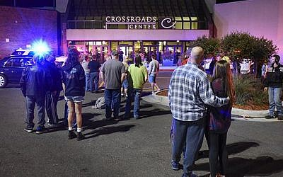 People stand near the entrance on the north side of Crossroads Center mall between Macy's and Target as officials investigate a reported multiple stabbing incident, Saturday, September 17, 2016, in St. Cloud, Minnesota. (Dave Schwarz/St. Cloud Times via AP)