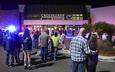 People stand near the entrance on the north side of Crossroads Center mall between Macy's and Target as officials investigate a reported multiple stabbing incident, Saturday, Sept. 17, 2016, in St. Cloud, Minnesota. (Dave Schwarz/St. Cloud Times via AP)
