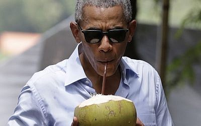 US President Barack Obama drinks from a fresh coconut along the banks of the Mekong River in the Luang Prabang, Laos, Wednesday, Sept. 7, 2016. (AP Photo/Carolyn Kaster)