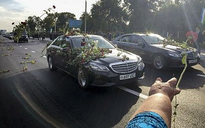 People throw flowers on limousines as they gather along a road to watch the funeral procession of President Islam Karimov in Tashkent, Uzbekistan, September 3, 2016. (AP/Umida Akhmedova)