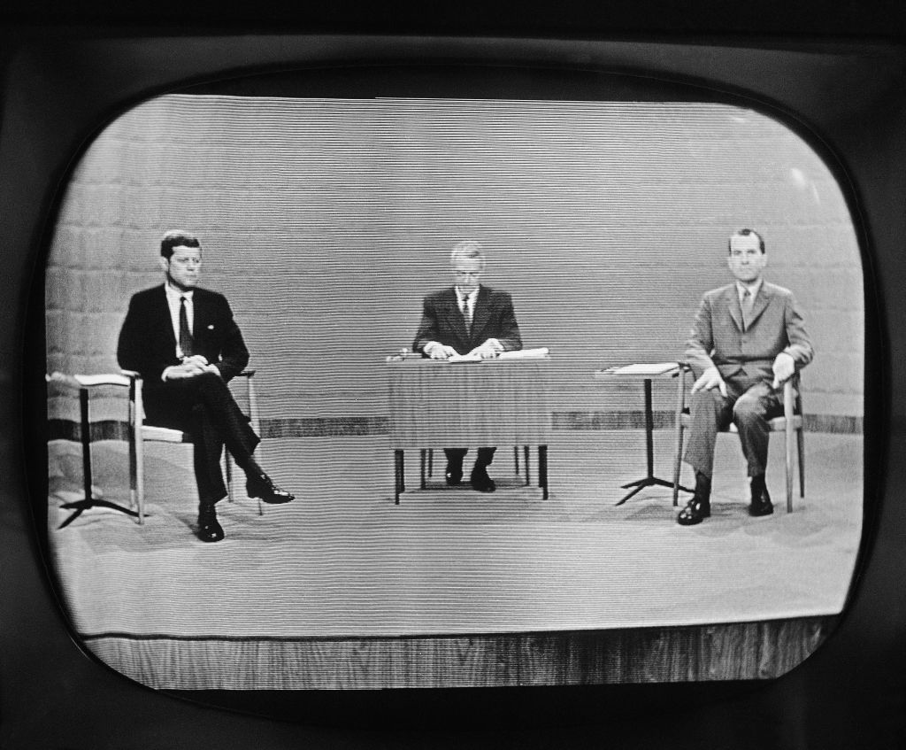 With moderator Howard K. Smith sitting between, Sen. John Kennedy, left, and Vice President Richard Nixon appear on television studio monitor set as their debate got under way, Sept. 26, 1960 in Chicago. (AP Photo)