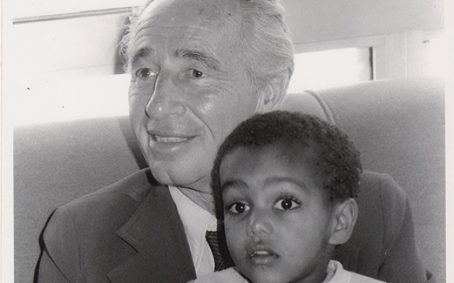 Prime minister Peres with a child brought to Israel in the 1984 Operation Moses, which brought Ethiopian Jews to Israel (Defense Ministry Archives)
