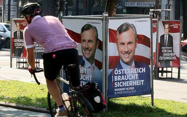 A man cycles between election posters of Alexander Van der Bellen, presidential candidate and former head of the Austrian Greens, left and right, and Norbert Hofer, candidate for Austria's right-wing Freedom Party, FPOE, center, in Vienna, Austria, Monday, Sept. 12, 2016.  (AP Photo/Ronald Zak)