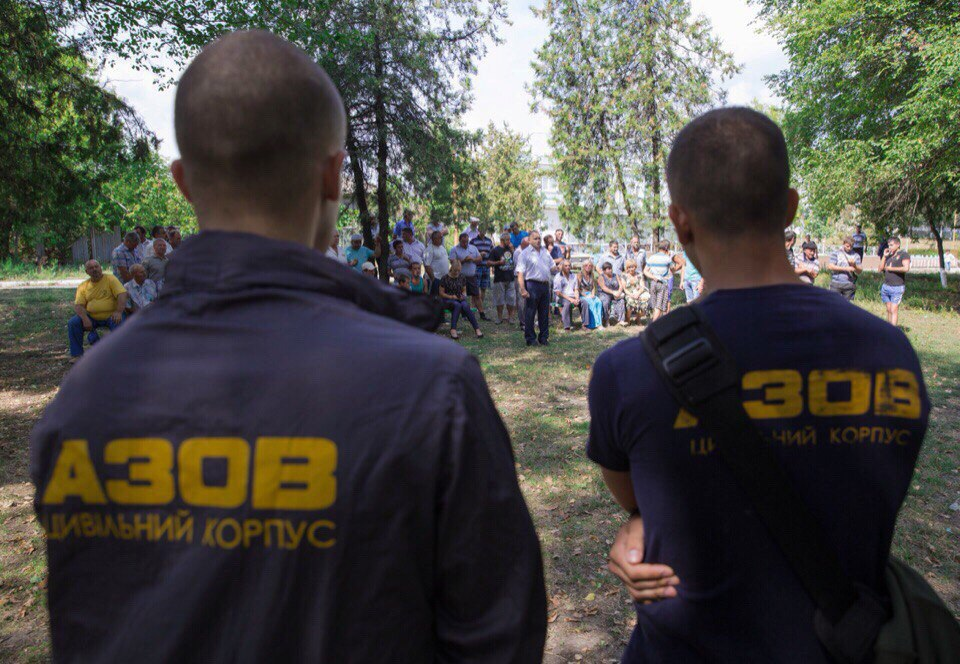 Members of the right-wing Azov neighborhood patrol watch a crowd gathered after the pogroms in Loshchynivka, Ukraine, caused 80 Roma residents to flee. (courtesy of Marianna Zlobina)