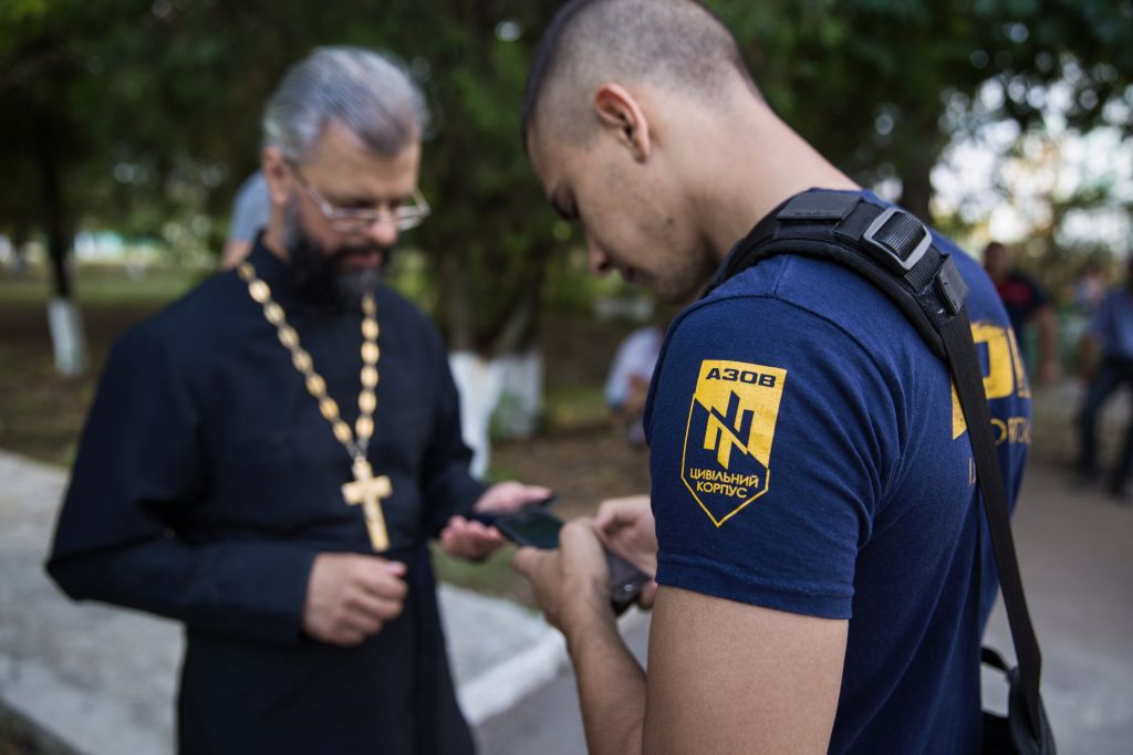 A member of the right-wing Azov group standing with a priest in Loshchynivka, Ukraine, a day after violent pogroms caused 80 Roma residents to flee. (courtesy of Marianna Zlobina)
