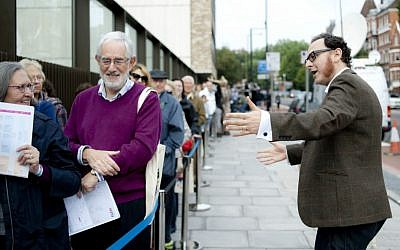 Raymond Simonson, chief executive of the JW3 community center in London, greets visitors at the JCC's opening in 2013. (Blake Ezra Photography via JTA)