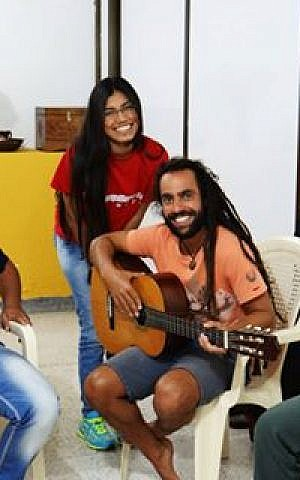 Musician Lior ben Hur playing guitar with members of the Barranquilla community. (Courtesy)