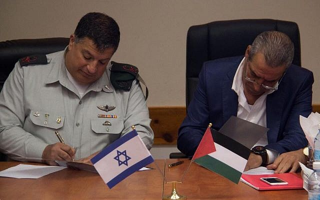 COGAT's Major General Yoav (Poly) Mordechai and the Palestinian Authority's Minister of Civil Affairs, Hussein al-Sheik sign a Memorandum of Understanding to upgrade the postal service system in Judea and Samaria, September 4, 2016 (COGAT)
