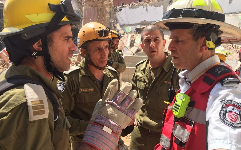 Representatives from the IDF Home Front Command's search and rescue unit speak with the head of the local fire department Eyal Caspi, right, at the site of a building collapse in the Ramat Hahayal neighborhood of Tel Aviv on September 5, 2016. (IDF Spokesperson's Unit)
