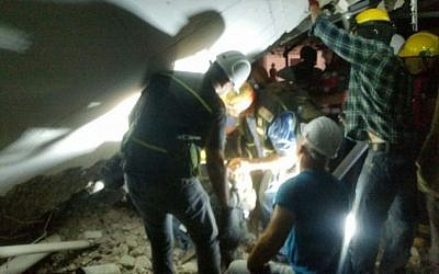Rescue workers attempt to evacuate people from a collapsed parking structure in the Ramat Hahayal neighborhood in northern Tel Aviv, September 5, 2016. (Israel Fire and Rescue Services)