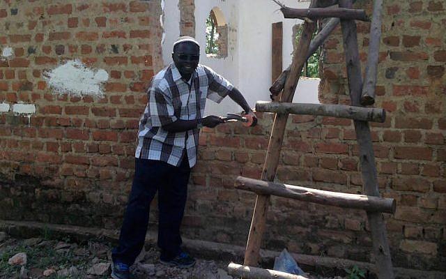 Rabbi Gershom Sizomu, leader of Uganda's Jewish community, dismantling the old synagogue in Nabagoye. (Courtesy of Be'chol Lashon via JTA)