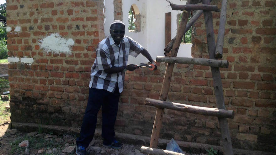 Rabbi Gershom Sizomu, leader of Uganda's Jewish community, dismantling the community's old synagogue in Nabagoye. (Courtesy of Be'chol Lashon via JTA)