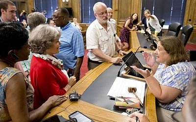 In this Aug. 9, 2016 file photo, Chairwoman Kathryn Lindley, right, is approached by people during the Guilford County Board of Elections meeting at the Old Guilford County Courthouse in Greensboro, N.C. (Joseph Rodriguez/News & Record via AP)