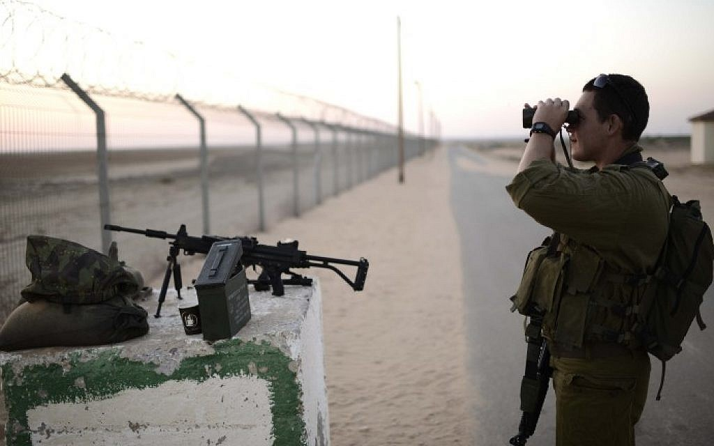 Illustrative. An IDF soldier from the 10th division looks through binoculars into Gaza from a nearby Israeli community on August 7, 2014. (Tomer Neuberg/Flash90)