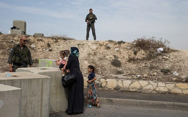Israeli Border Police block the entrance to the East Jerusalem neighborhood of Issawiya, checking Palestinians wanting to pass, on October 20, 2015. Following the recent wave of terror attacks in Jerusalem and Israel, Israel Police is blocking East Jerusalem neighborhoods checking for knives and anything that can be used as a weapon. (Nati Shohat/Flash90)