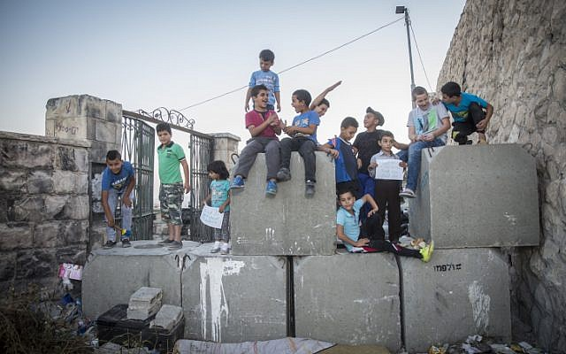 Palestinian children pose for a photo on top of cement blocks placed by the Israeli army in the East Jerusalem neighborhood of Ras al Amud, on October 21, 2015. (Hadas Parush/Flash90)