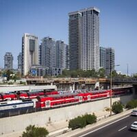 An Israel Railways train passes the Ayalon Highway, near the Arlozorov Street 'Central' train station in Tel Aviv, August 23, 2016. (Miriam Alster/Flash90)
