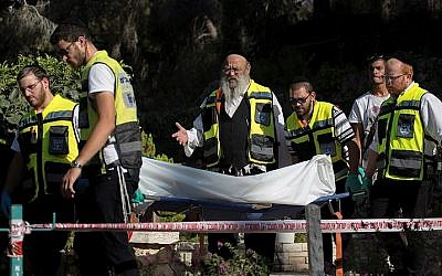 Zaka rescue personnel carry a body at the scene where a bereaved father committed suicide on his son's grave at the military cemetery on Mount Herzl, August 2, 2016. (Yonatan Sindel/Flash90)