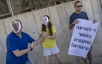 Activists, including two with masks of Benjamin Netanyahu and Yisrael Katz, protest against the decision to cancel all infrastructure work planned by Israel Railways on Shabbat on September 4, 2016. Yonatan Sindel/Flash90)