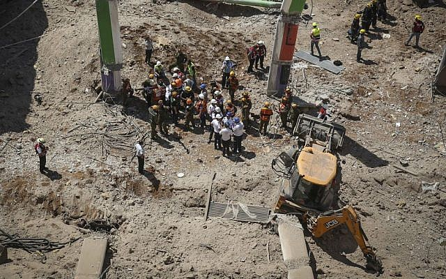 Rescue workers stand beside a tractor that is believed to have caused the collapse of a parking structure in the Ramat Hahayal neighborhood in northern Tel Aviv, killing two, on September 5, 2016. (Miriam Alster/Flash90)