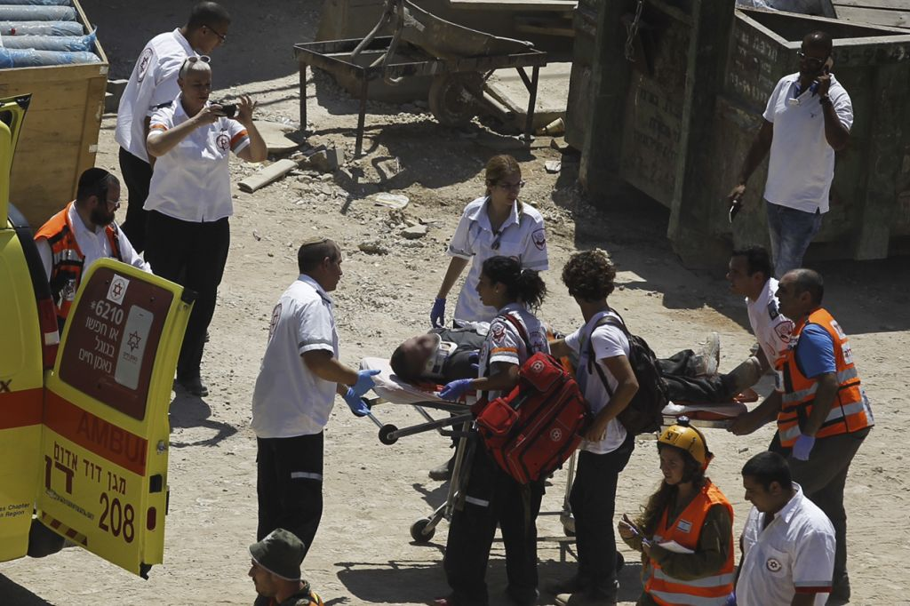 Rescue workers evacuate a wounded man at the site where a building collapsed in Tel Aviv on September 5, 2016. (Miriam Alster/Flash90)
