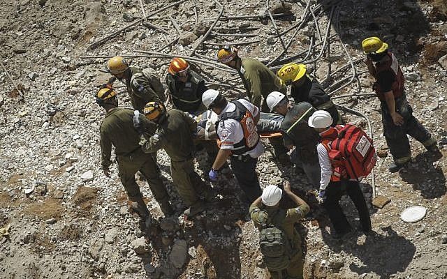 Rescue workers evacuate a wounded man from a collapsed parking structure in the Ramat Hahayal neighborhood in northern Tel Aviv, September 5, 2016. (Miriam Alster/Flash90)