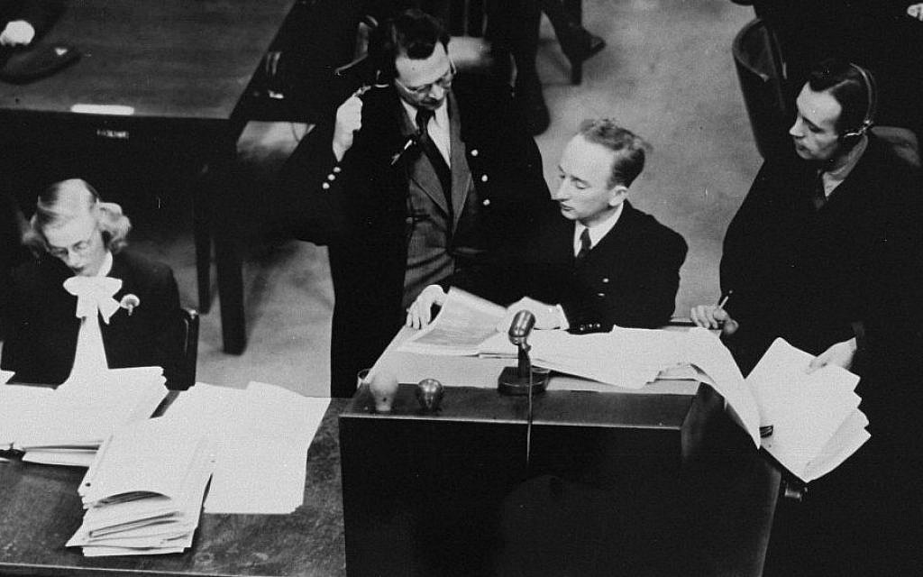 Chief prosecutor Benjamin Ferencz presents documents as  evidence at the Einsatzgruppen Trial.  Ferencz is flanked by German defense lawyers, Dr. Friedrich Bergold (right, counsel for Ernst Biberstein) and Dr. Rudolf Aschenauer (left, counsel for Otto Ohlendorf), who are protesting the introduction of the evidence. (USHMM/ Ben Ferencz)