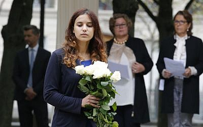 An unidentified relative of victims is to lay flowers during a ceremony for victims of terrorism in Paris, Monday Sept.19, 2016. (AP Photo/Michel Euler, Pool)