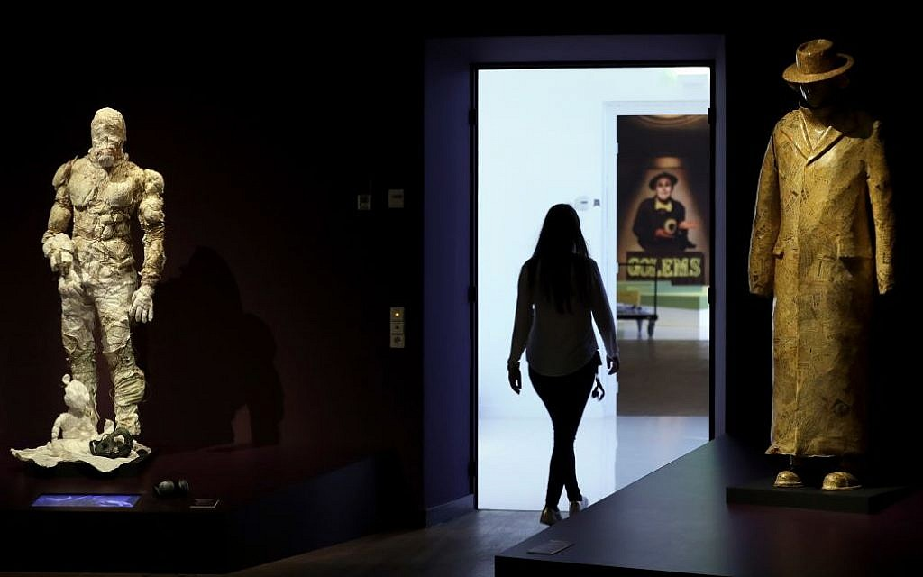 A woman walks past a Golem costume of the Malenki Theater in Tel Aviv, left, and a Golem sculpture of the Schaubuehne Theatre in Berlin for 'Death, Destruction and Detroit II', right, during a press presentation for the 'Golem' exhibition at the Jewish Museum in Berlin, Germany, Thursday, September 22, 2016. (AP Photo/Michael Sohn)