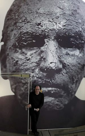 A man walks through a door covered by a giant photo, titled 'Golem', by photographer Joachim Seinfeld during a press presentation for the 'Golem' exhibition at the Jewish Museum in Berlin, Germany, Thursday, Sept. 22, 2016. (AP Photo/Michael Sohn)