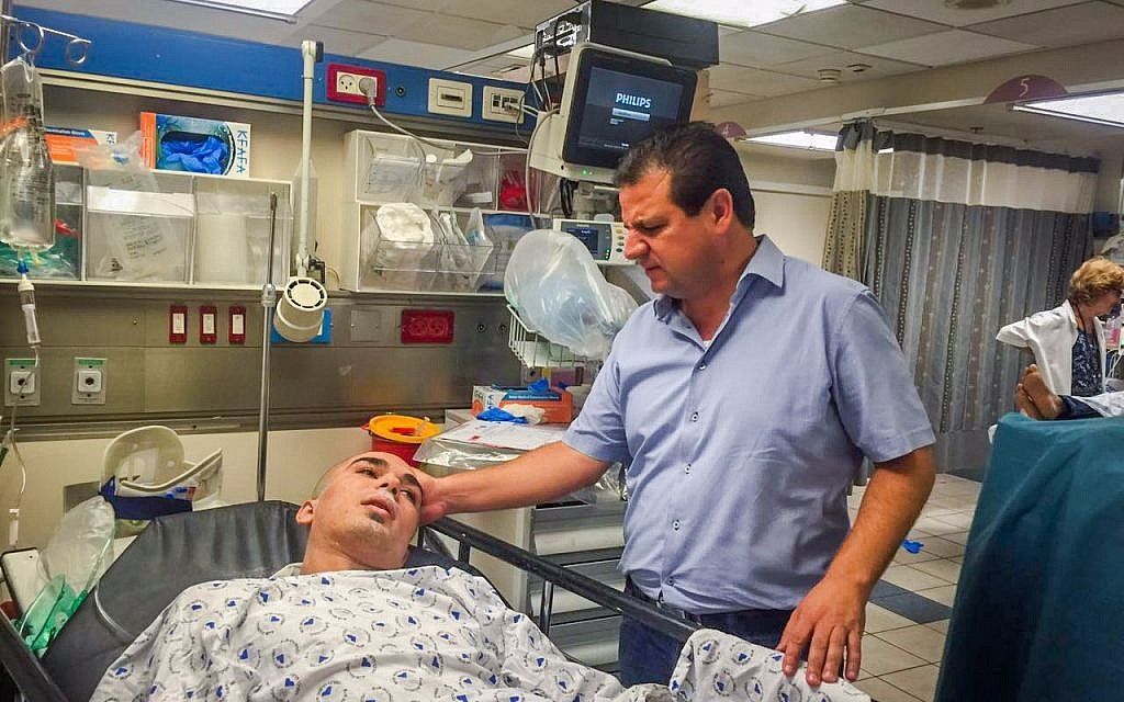 MK Ayman Odeh of the Joint Arab list visits a man wounded in a Tel Aviv building collapse, at the Ichilov Hospital on Monday, September 5, 2016 (Joint List)