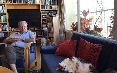 Amos Oz and his cat, in his Tel Aviv living room in September 2016 (Jessica Steinberg/Times of Israel)