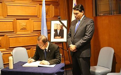 UN Secretary General Ban Ki-Moon, seated, signs a commemoration book for former Israeli president Shimon Peres at a memorial ceremony held at UN Headquarters in New York, September 29, 2016. Standing is Israel's envoy to the world body Danny Danon. (Courtesy)