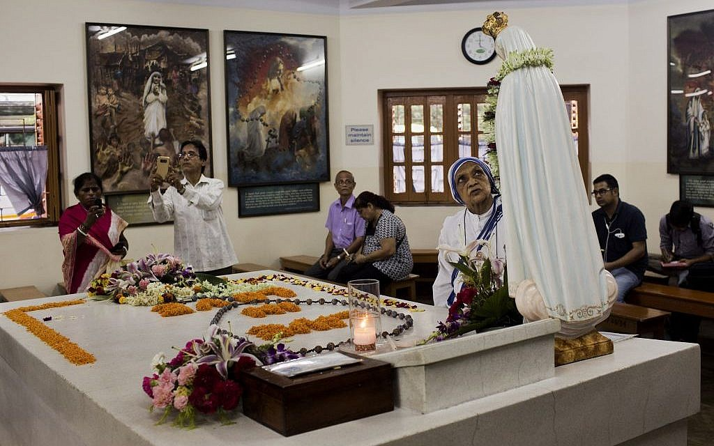 Worshippers gather around the tomb of Mother Teresa inside the Mother house in Kolkata, India, in Kolkata, India, on September 3, 2016. (Bernat Armangue/AP Photo)