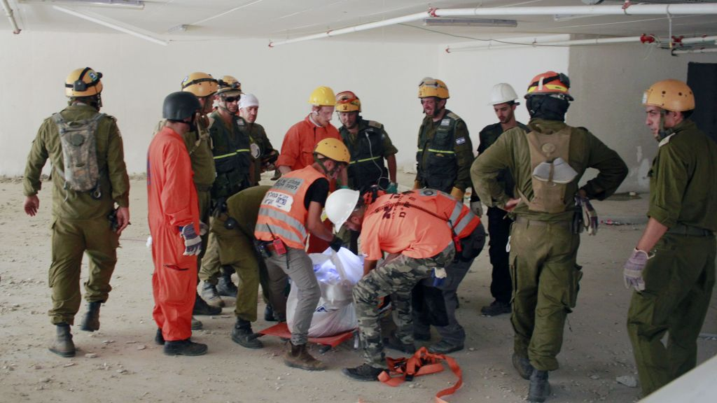 Search and rescue workers remove a third body from the rubble of a collapsed parking garage in Tel Aviv on September 6, 2016. (Judah Ari Gross/Times of Israel)