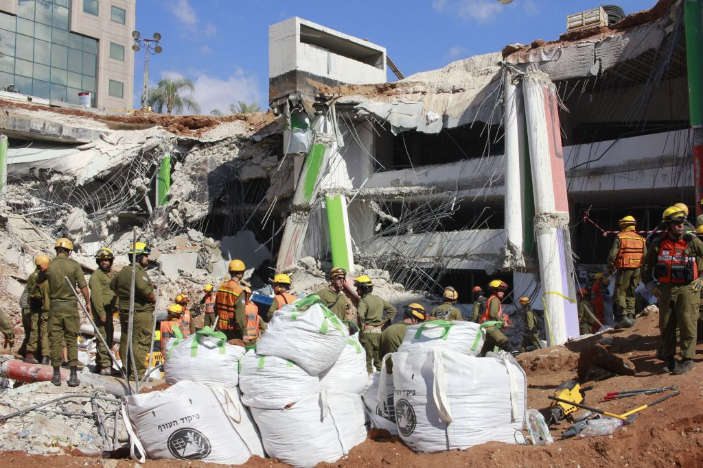 Soldiers in the IDF Home Front Command take part in the rescue effort at a collapsed parking garage in Tel Aviv's Ramat Hahayal neighborhood on September 6, 2016. (Judah Ari Gross/Times of Israel)