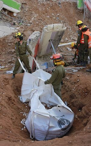 Soldiers in the IDF Home Front Command fill bags with rubble during the rescue effort at a collapsed parking garage in Tel Aviv's Ramat Hahayal neighborhood on September 6, 2016. (Judah Ari Gross/Times of Israel)