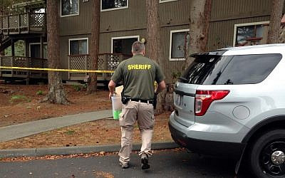 Investigators are seen at the apartment complex that has been tied to Arcan Cetin, the alleged Cascade Mall shooter, in Oak Harbor, Washington, September 25, 2016. Authorities carried boxes from a rear, upstairs apartment in the four-unit building. (AP Photo/Martha Bellisle)