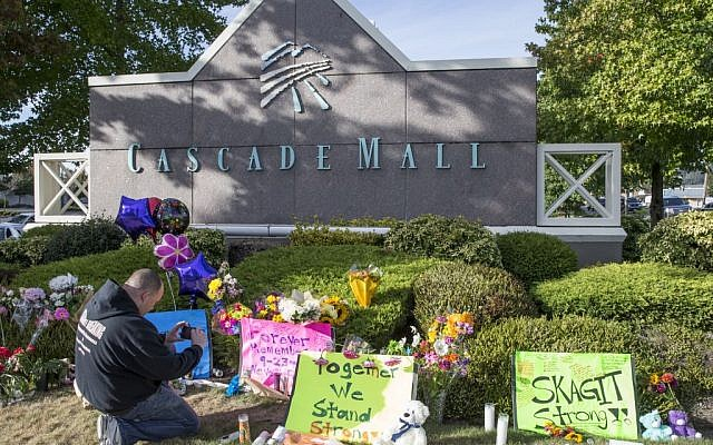 Chris Nelson of Burlington, Washington, takes a picture of a memorial on September 25, 2016, in Burlington, to five victims killed in a shooting on Friday at a Cascade Mall.  (AP Photo/Stephen Brashear)
