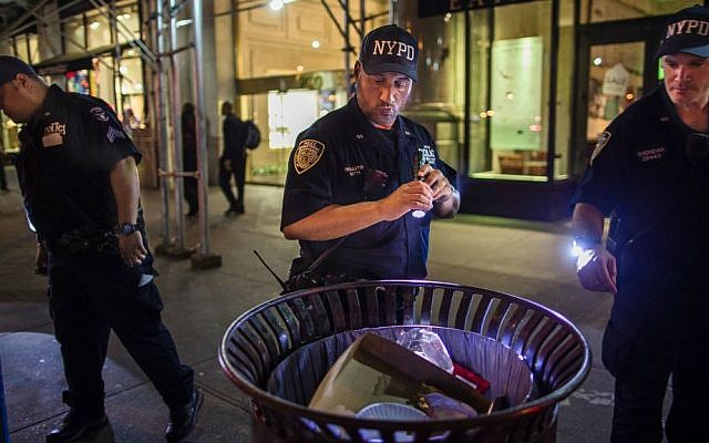 Police officers look for suspicious packages along Fifth Avenue near the scene of an explosion on West 23rd Street and 6th Avenue in Manhattan's Chelsea neighborhood, in New York, early Sunday, Sept. 18, 2016. (AP Photo/Andres Kudacki)