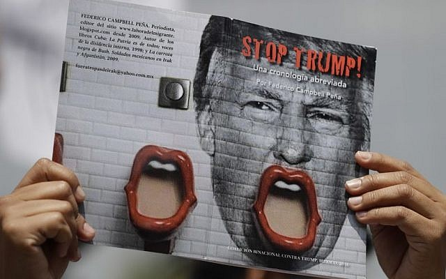 """A demonstrator protesting Donald Trump's meeting with the Mexican president holds up a book jacket with the title; """"Stop Trump!"""" during a morning protest at the Angel of Independence Monument that drew just a handful of people, in Mexico City, Wednesday, Aug. 31, 2016. (AP/Rebecca Blackwell)"""
